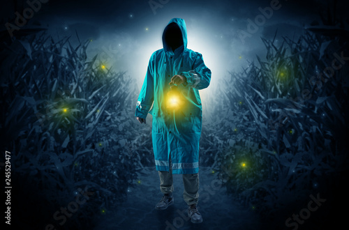 Obraz na płótnie Man in raincoat at night coming from thicket and looking something with glowing