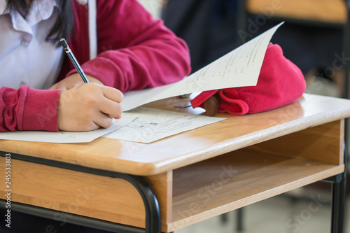 High school university student holding pencil writing exam on paper answer sheet, writing examination room doing final test in classroom with thai uniform Canvas Print