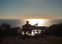 The Young Man With Bicycle Sitting On A Mountain Watching The Sunset