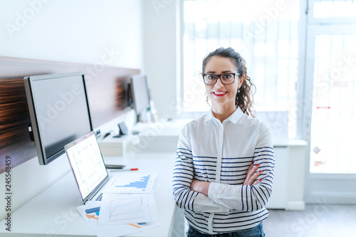 Fotomural Smiling businesswoman dressed casual and with eyeglasses and ponytail standing in the modern office with arms crossed