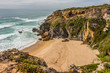 Wild sandy beach with cliffs on Atlantic Ocean coast, Rota Vicentina, Alentejo, Portugal. Small waves hitting the rocks.