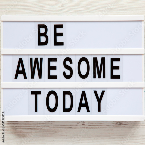 Photo  'Be awesome today' word on modern board over white wooden surface, from above