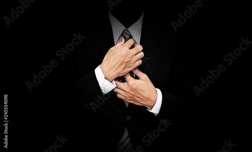 Tela Businessman in black suit tying necktie, on black background