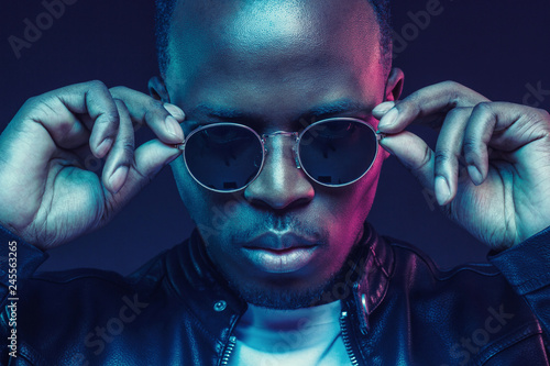 Close-up studio shot of african american male model wearing trendy sunglasses and leather jacket
