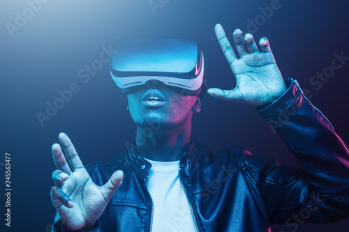 Young african man wearing virtual reality goggles with hands up, isolated on black background - 245563477