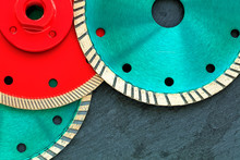 Several Diamond Cutting Wheels Of Red And Emerald Color Against A Background Of Gray Granite.