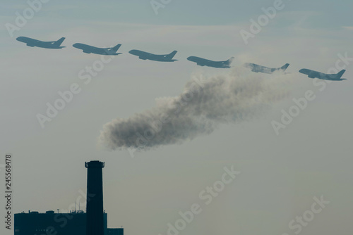 Fotografie, Obraz  Multiple exposure of plane taking off, plane crossing smoke of power plant
