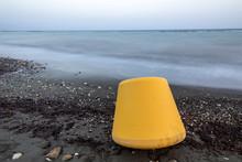 Yellow Buoy Lying On The Sea Coast