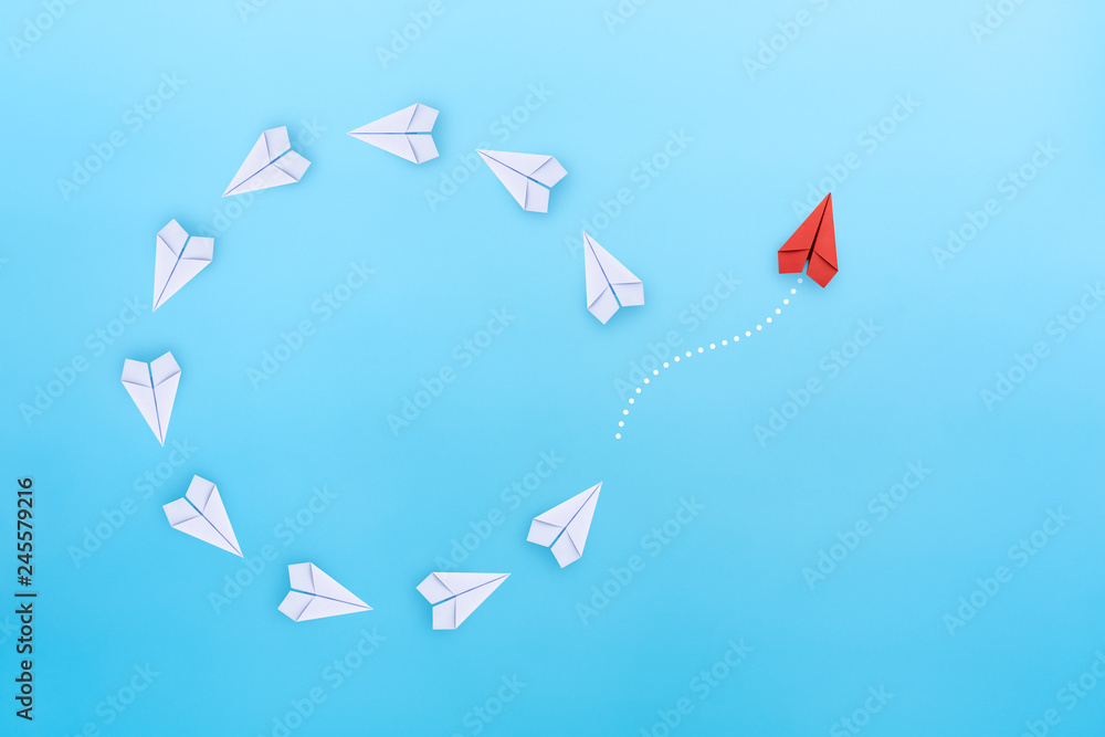 Fototapeta Group of white paper planes fly in a circle and one red paper plane pointing in different way on blue background. Business for new ideas creativity, innovative and solution concept.