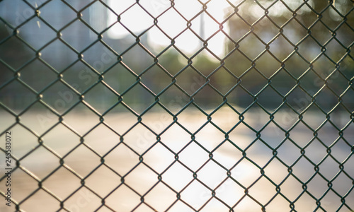 Fotografia  Close-up chain link fence , Sunset background