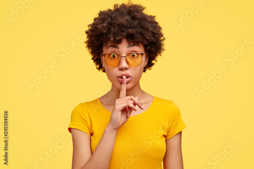 Obraz na plátně Stupefied secret dark skinned woman makes gesture quietly, asks remain silent, gossips about something, looks mysteriously as tells secret, wears bright yellow t shirt, stands indoor