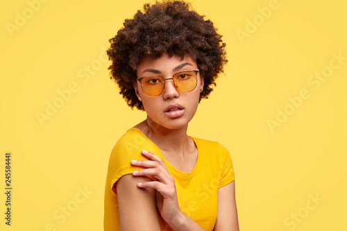 Sideways shot of calm serious emotionless woman keeps arms crossed, wears yellow t shirt and shades, has frizzy hair, being without emotions, has natural beauty Slika na platnu