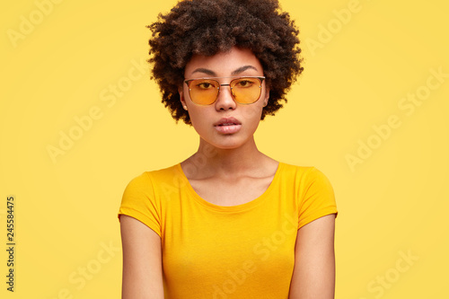 Fotografering  Cropped shot of serious attractive woman with curly hair, gazes thoughtfully at