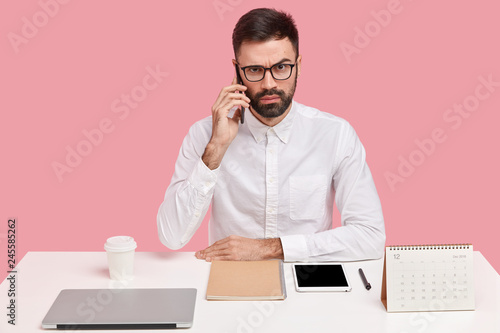 Strict angry male boss calls on digital smart phone, does remote work, consults Tablou Canvas