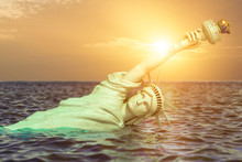 Destroyed Statue Of Liberty In The Sunset Half Covered By Rising Ocean Level.  Apocalypse Of USA, America And The End Of Civilization Concept.