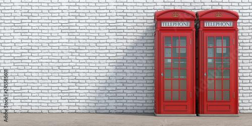 Obraz Red phone booth on brick wall background. London, british and english symbol. - fototapety do salonu