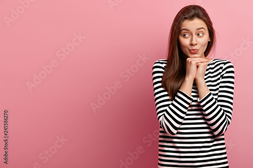 Indoor shot of attractive young lady keeps hands under chin, concentrated aside, Fototapet