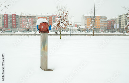 Fotografie, Obraz  Old fire hydrant for firefighters on the street in the city with snow in the win