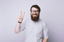 Peace. Bearded Man In Glasses And Shirt Is Gesturing Victory Sign