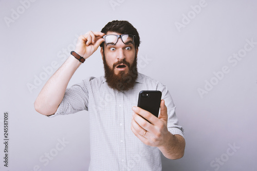 Bearded man using smartphone scared in shock with surprised face with fear expre Fototapet