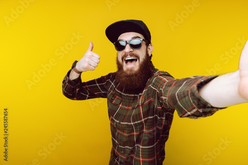 Valokuva  Like ! Bearded guy taking selfie in black hat and sunglasses and gesturing thumb