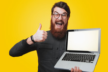 Handsome Excited Bearde Man Holding His Laptop And Gesturing Thumb Up Over Yellow Background