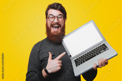 Photo  Happy bearded man in glasses holding and pointintg at laptop while looking at ca
