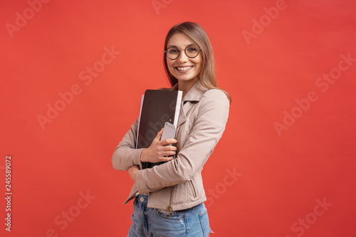 Obraz na płótnie Young smiling student or intern in eyeglasses standing with a folder on red background