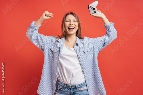 Photo  Competitive girl celebrates winning holding game joystick controller on red background