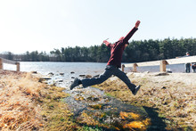 Boy Jumping Over A Stream. Agile Child Outside