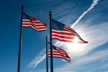 3 American Flags Against A Blue Sky