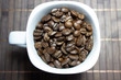 Kaffeebohnen in einer weißen Tasse mit dunklem Hintergrund