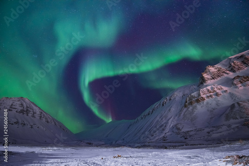 Aurore polaire The polar arctic Northern lights aurora borealis sky star in Norway travel Svalbard in Longyearbyen city the moon mountains