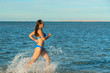 A sexy young brunette woman or girl wearing a bikini running through the surf on a deserted tropical beach with a blue sky. Young woman running by the sea.