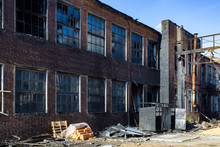 Consequences Of Fire. Burnt Industrial Or Office Building Of Red Brick. Broken Windows, Walls In Black Soot
