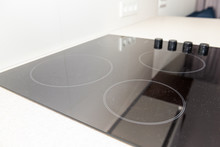 Macro Closeup Of Modern Luxury Electric Cook Stove Top Stovetop Cooktop With Glass Reflection And Circles Background In Empty Home