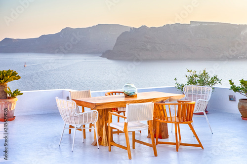 Foto auf Gartenposter Santorini Tranquil and Romantic Atmosphere at Open Air Terrace Restaurant in Beautiful Oia Village on Santorini Island in Greece in Front of Volcanic Caldera Mountain.