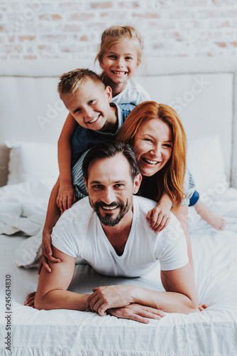 Fototapeta Smiling man and woman laying on bed with kids obraz