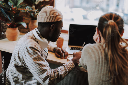 Rare view of the Afro-American man making notes with his friend - 245642216