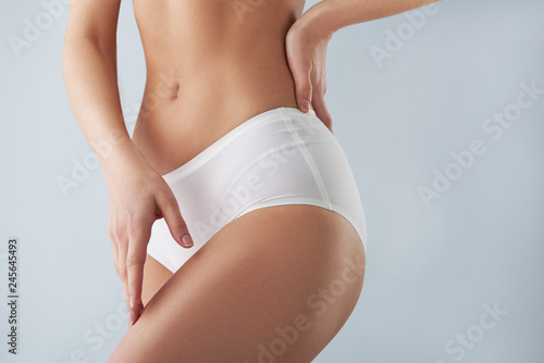 Obraz Young woman in white panties touching her leg - fototapety do salonu