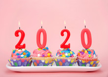 White Cupcakes With Rainbow Colored Frosting And Brightly Colored Star Candies On A Rectangular Plate Pink Background With 2020 Candles Burning. Happy New Year Theme.