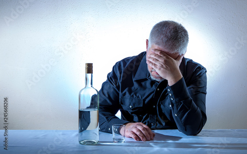 Fotografía  a man is desperately sitting at a table with a bottle of alcohol