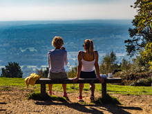 LEITH HILL, DORKING, SURREY, ENGLAND - OCTOBER 10, 2018: Two Women On A Bench Drinking And Looking At The View Across The Surrey Countryside On A Sunny Autumn Day
