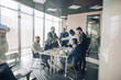 Multiracial team of business partners of different age interacting in boardroom of modern spacious and well-lit office, being viewed through transparent glass wall.