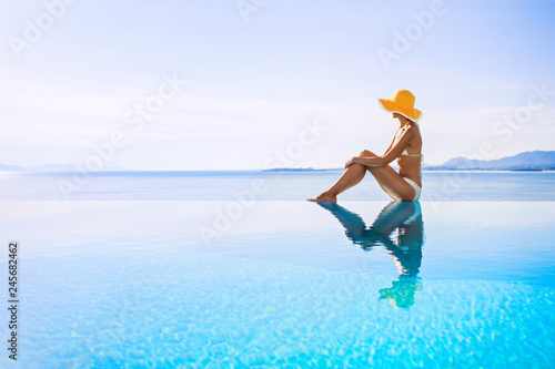 Valokuva  Young woman enjoying a sun in the luxury infinity pool