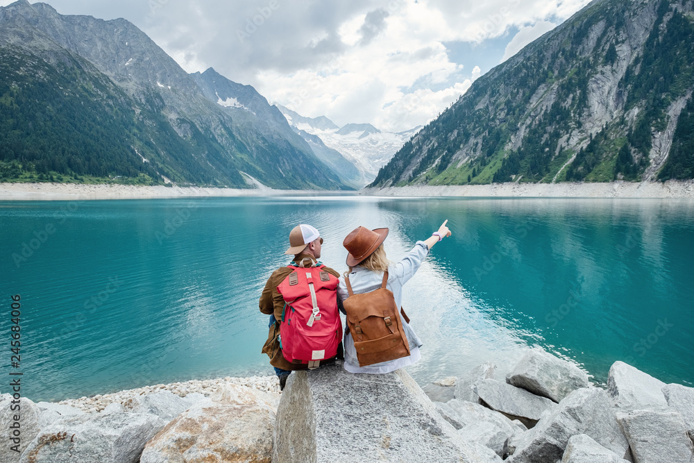 Fototapeta Travelers couple look at the mountain lake. Travel and active life concept with team. Adventure and travel in the mountains region in the Austria. Travel - image