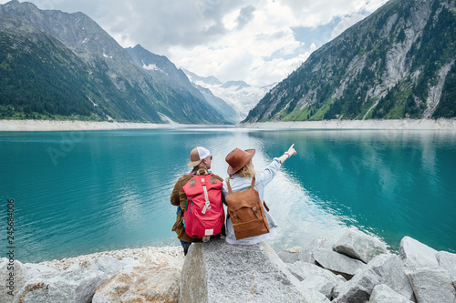 Aluminium Prints Green blue Travelers couple look at the mountain lake. Travel and active life concept with team. Adventure and travel in the mountains region in the Austria. Travel - image