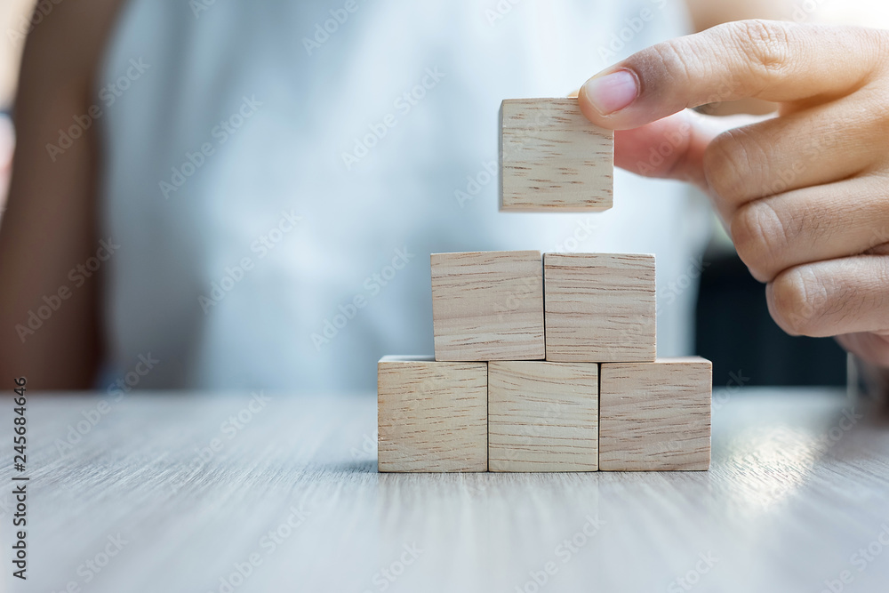 Fotografía  Businesswoman hand placing or pulling wooden block on the building