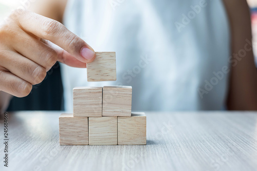 Fotografiet  Businesswoman hand placing or pulling wooden block on the building