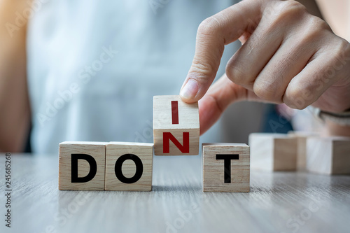 Photo  Businesswoman hand holding wooden cube with flip over block DON T to DO IT word on table background